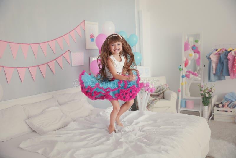 跳跃在床上的逗人喜爱的女孩在为生日庆祝装饰的屋子里 免版税库存图片