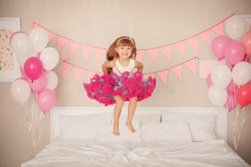 跳跃在床上的逗人喜爱的女孩在为生日庆祝装饰的屋子里 库存图片