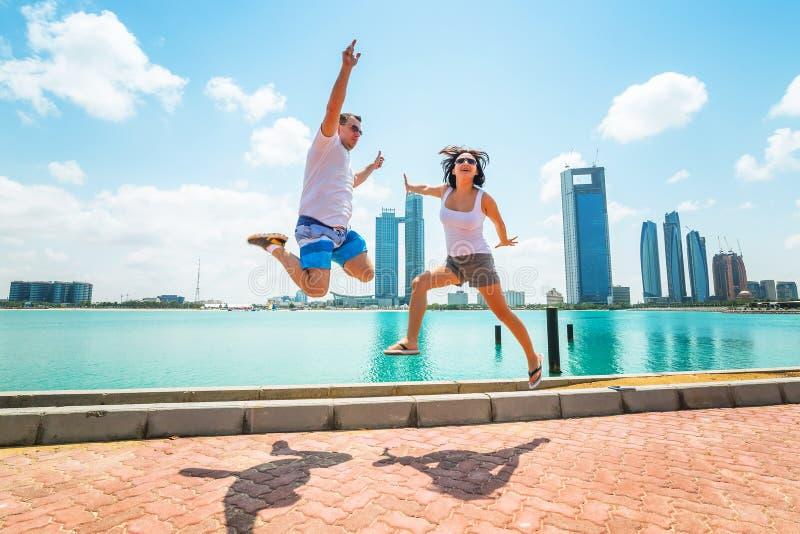 跳跃在度假的愉快的夫妇在阿布扎比 免版税库存照片