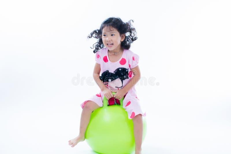 跳跃在弹跳球的愉快的孩子女孩 免版税库存图片