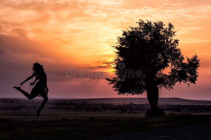 跳跃在日落光的一个美丽的女孩的剪影在树附近 免版税图库摄影