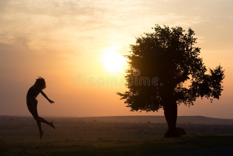 跳跃在日落光的一个美丽的女孩的剪影在树附近 库存照片