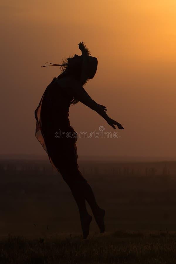 跳跃在日落光的一个美丽的女孩的剪影 图库摄影