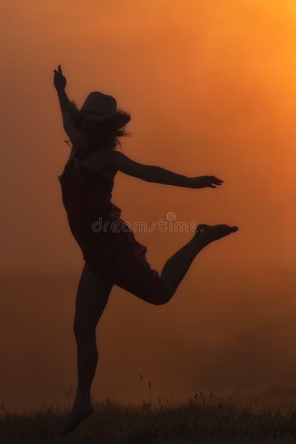 跳跃在日落光的一个美丽的女孩的剪影 免版税库存照片