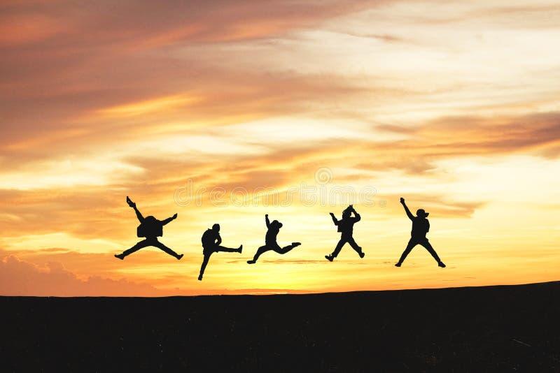 跳跃在日落和云彩的朋友剪影在小山与拷贝空间,事务 免版税库存照片