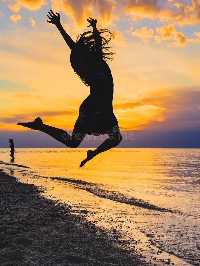 跳跃在日落的女孩的剪影 库存照片