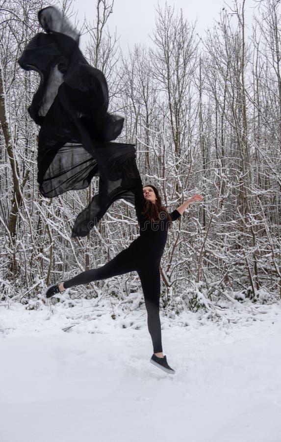 跳跃在有一块黑布料的多雪的森林里的黑芭蕾衣服的年轻女人在天空中 库存照片