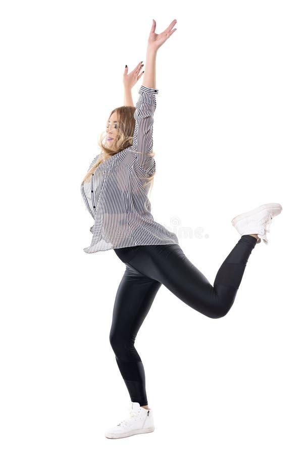 跳跃在有被举的胳膊的一条腿的快乐的偶然妇女爵士乐舞蹈家  库存照片