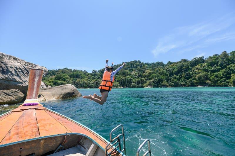 跳跃在木小船的妇女游人在热带海 免版税图库摄影