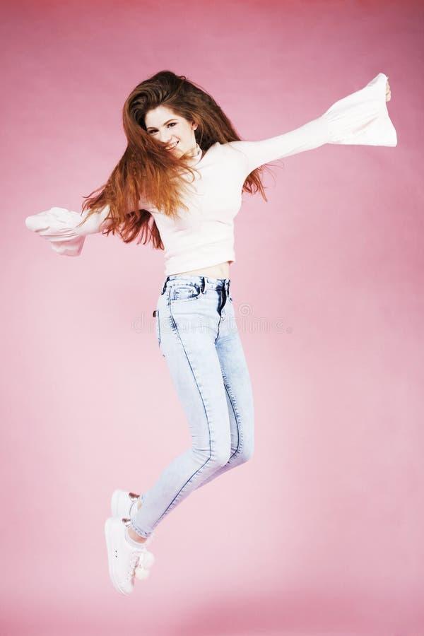 跳跃在桃红色背景,生活方式的年轻人相当红色头发姜女孩飞行青少年的人民愉快微笑 免版税库存图片