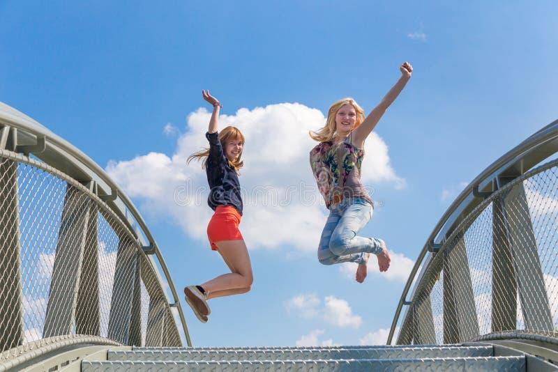 跳跃在桥梁的两个热心女孩 免版税库存照片
