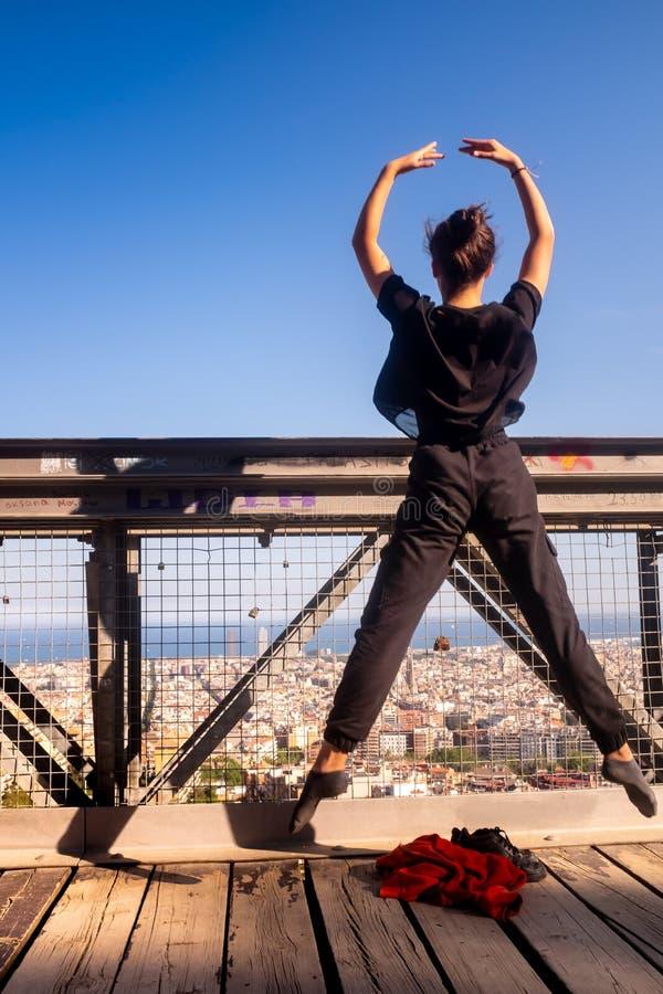 跳跃在桥梁的空中,都市风景的年轻舞蹈家在背景中 免版税图库摄影