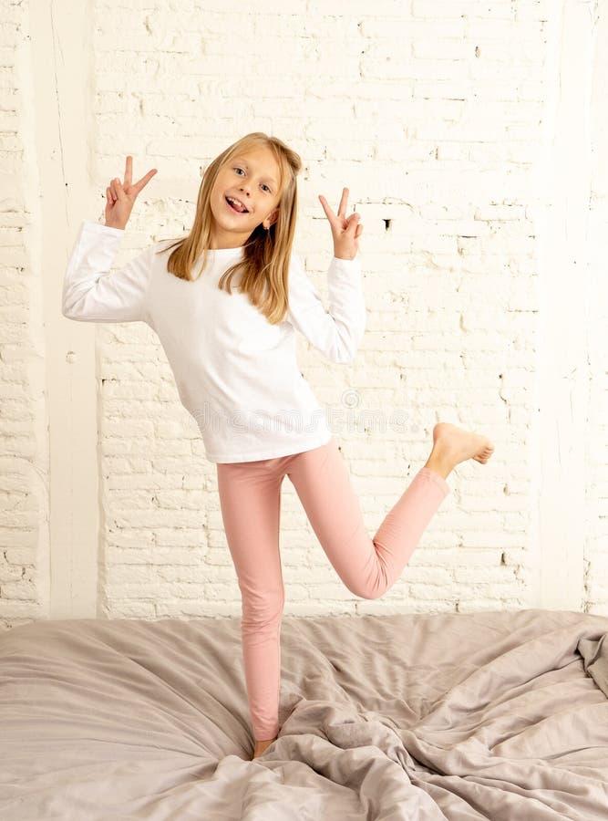 跳跃在正面情感和儿童幸福概念的床上的愉快的滑稽的女孩 库存照片