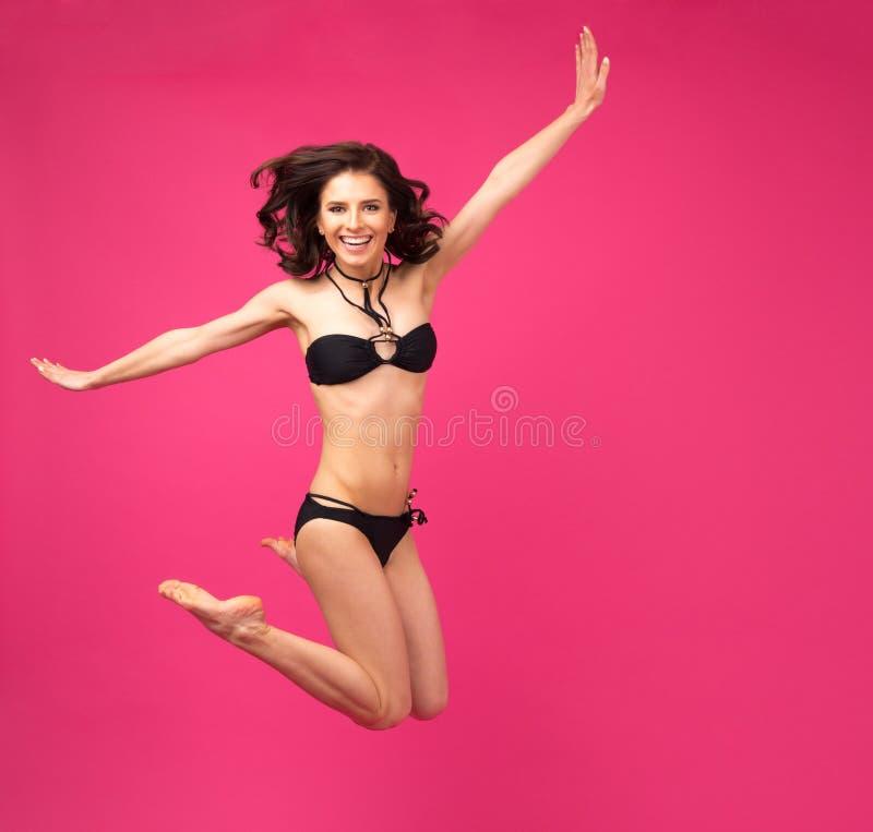 跳跃在比基尼泳装的愉快的妇女 库存图片