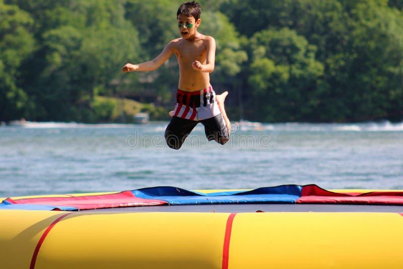 跳跃在水绷床的英俊的逗人喜爱的男孩漂浮在一个湖在密执安在夏天期间 库存照片