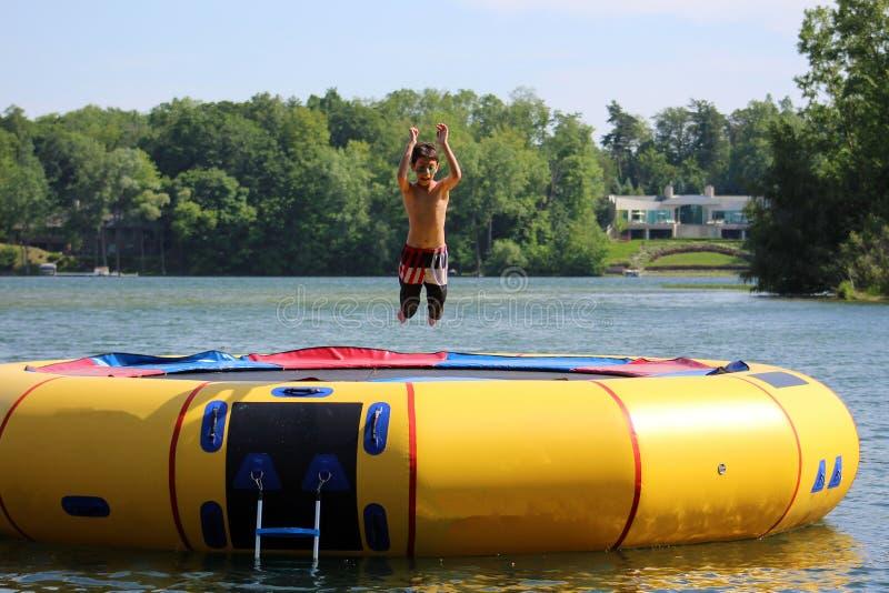 跳跃在水绷床的英俊的逗人喜爱的男孩漂浮在一个湖在密执安在夏天期间 免版税库存图片