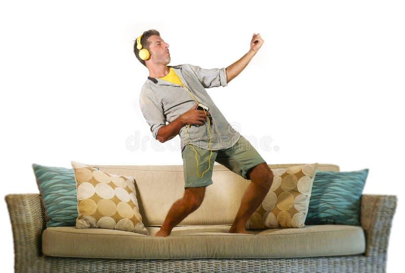 跳跃在沙发长沙发的年轻愉快和激动的人听到与演奏Air Guitar疯狂的hav的手机和耳机的音乐 免版税库存照片