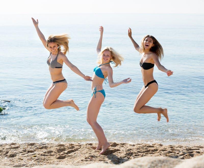 跳跃在沙滩的三个少妇 免版税库存图片