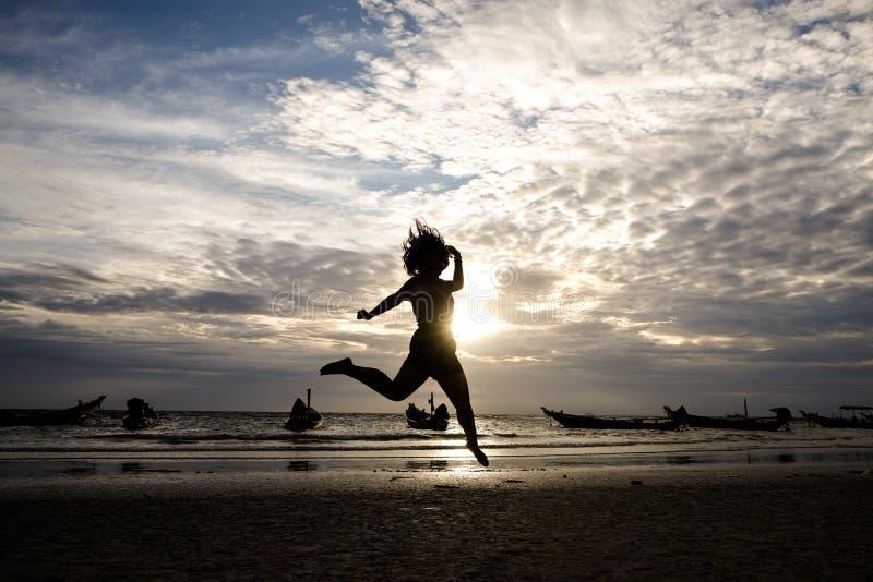 跳跃在海日落的愉快的妇女 免版税库存照片
