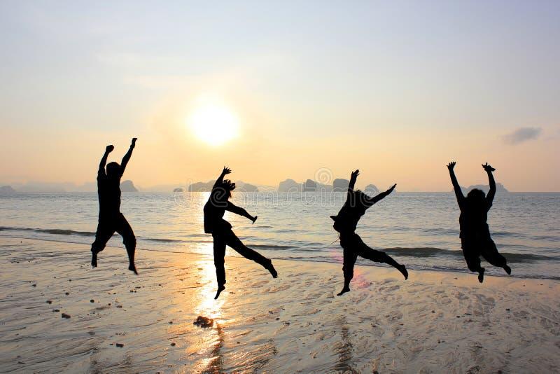 跳跃在海滩的愉快的友谊 库存照片