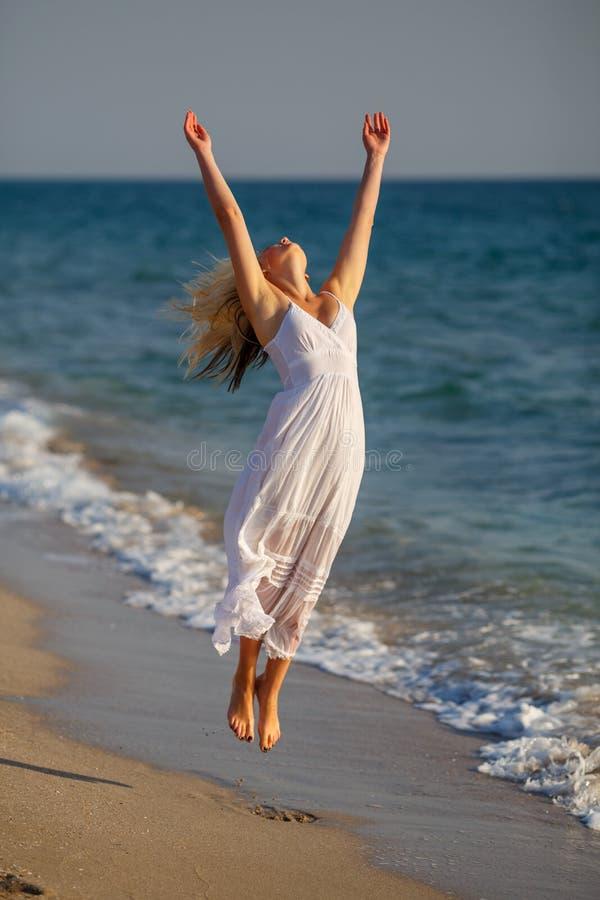 跳跃在海滩的白色礼服的美丽的愉快的妇女在一个晴天 免版税库存照片