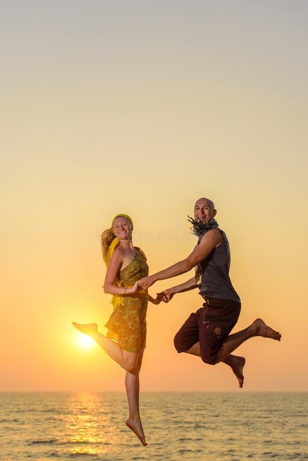 跳跃在海的背景的天空中和看照相机的人和女孩 在海滩的年轻愉快的夫妇跃迁在 库存图片