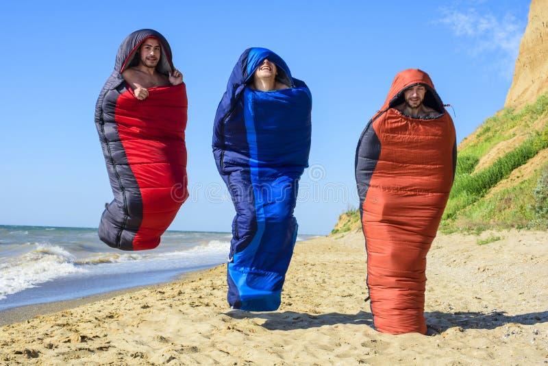 跳跃在海边的睡袋的小组欢呼的远足者 免版税库存照片