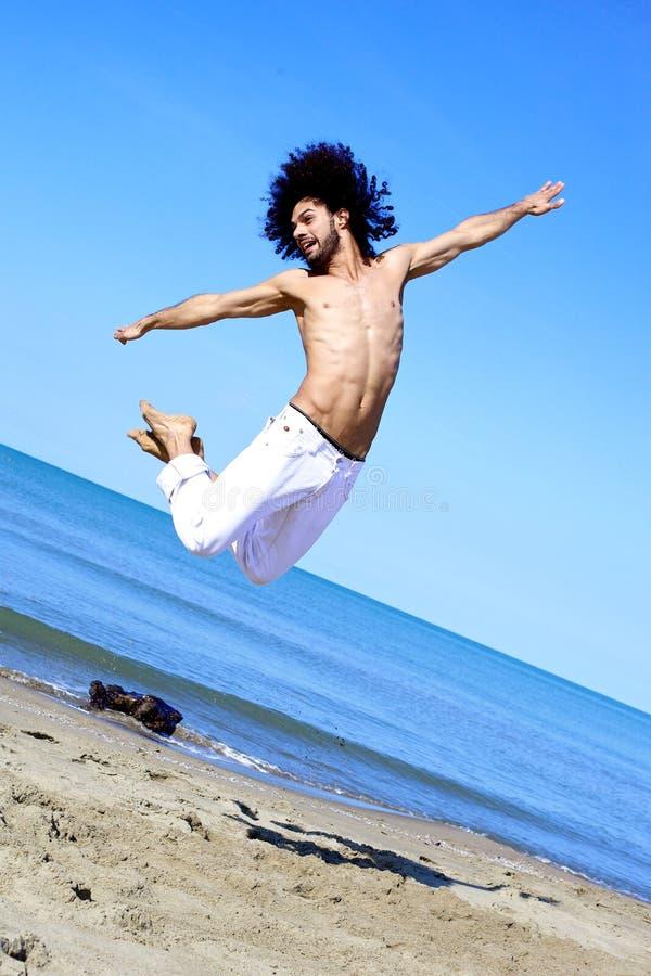跳跃在海滩前面的天空的惊人的舞蹈家 库存图片