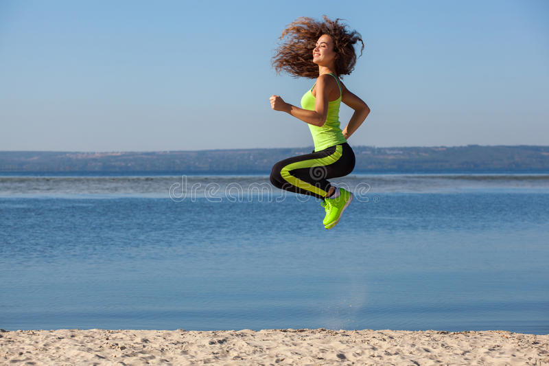 跳跃在海滩的体育期间的可爱的美丽的运动员早晨 库存照片