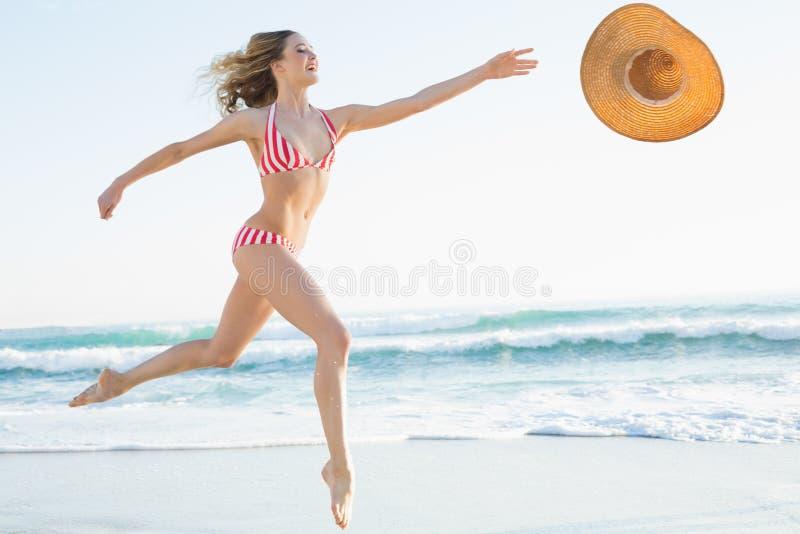 跳跃在海滩的典雅的少妇 库存图片