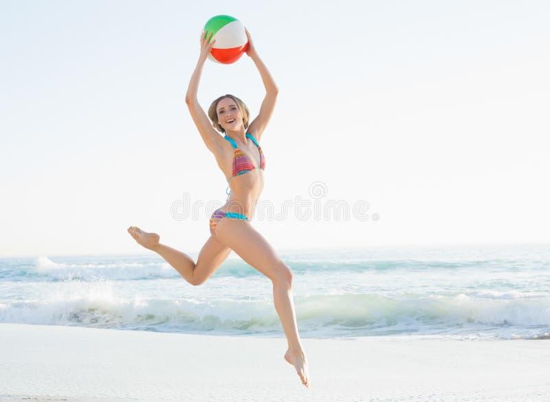 跳跃在海滩的华美的少妇拿着海滩球 免版税库存照片