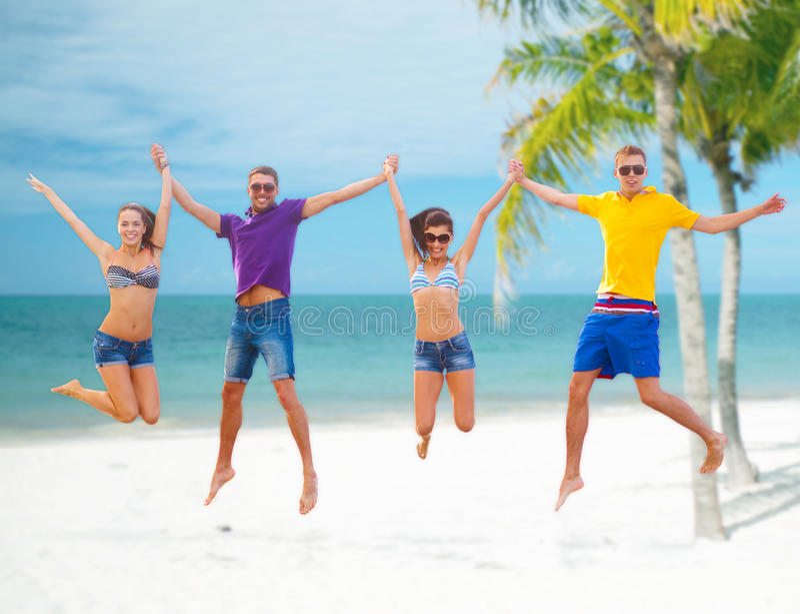 跳跃在海滩的小组朋友或夫妇 免版税库存照片