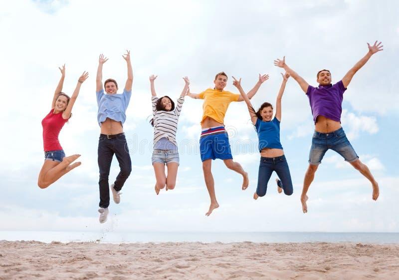 跳跃在海滩的小组朋友 免版税库存照片