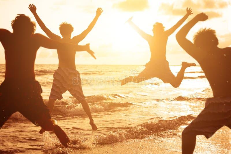 跳跃在海滩的小组青年人 免版税库存图片