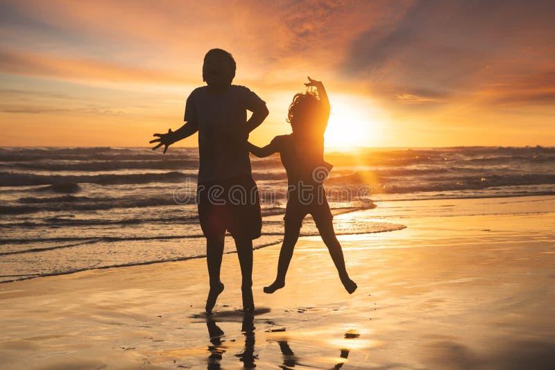 跳跃在海滩的快乐的孩子 库存图片