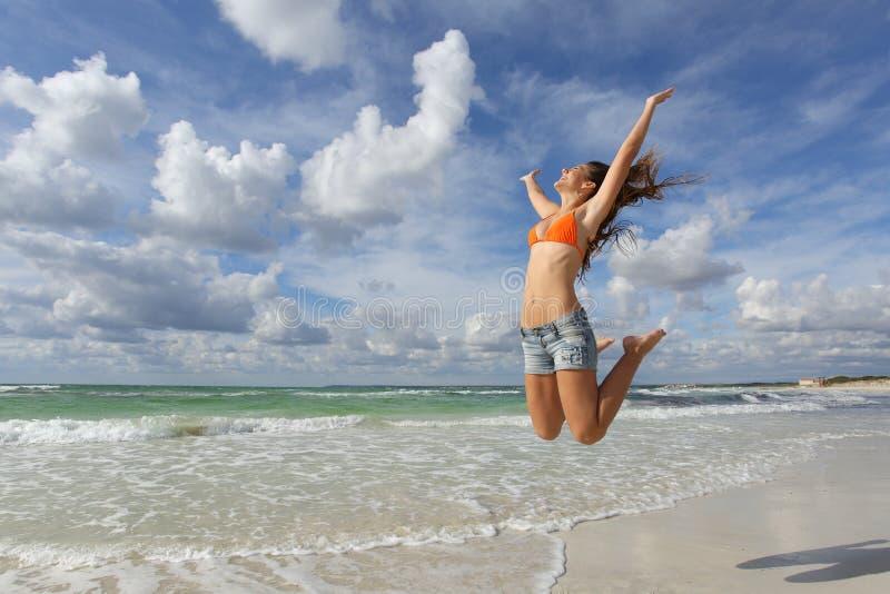 跳跃在海滩的愉快的女孩在度假 免版税库存照片