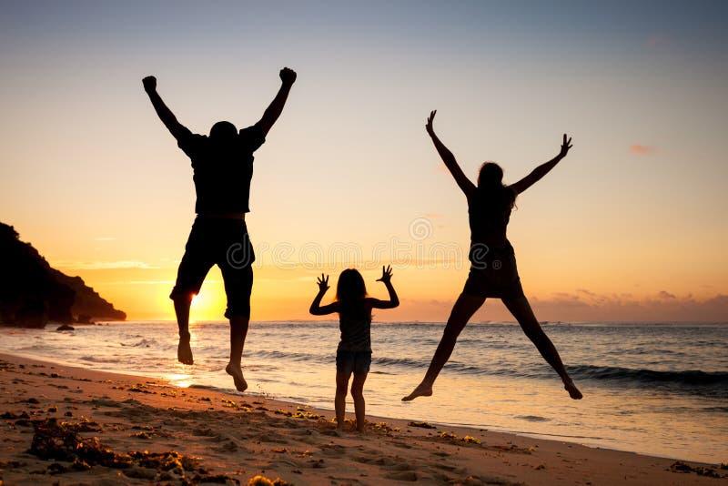 跳跃在海滩的愉快的家庭 免版税库存图片