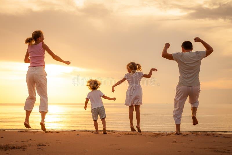 跳跃在海滩的愉快的家庭 库存图片