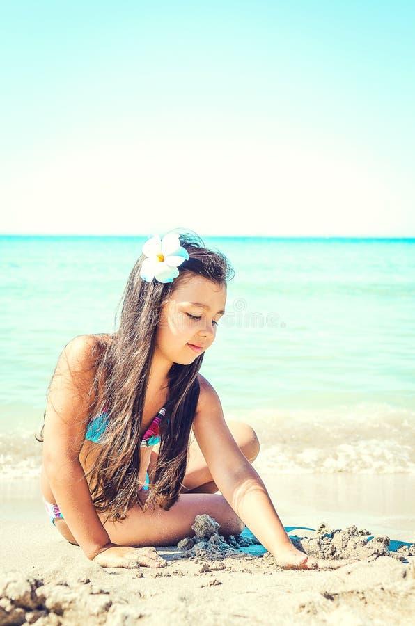 跳跃在海滩的愉快的小女孩 免版税库存照片