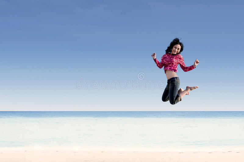 跳跃在海滩的美丽的女孩 库存图片