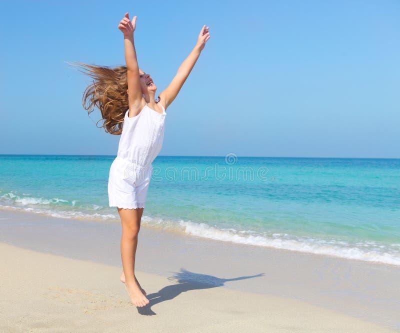 跳跃在海滩的逗人喜爱的小女孩 免版税图库摄影