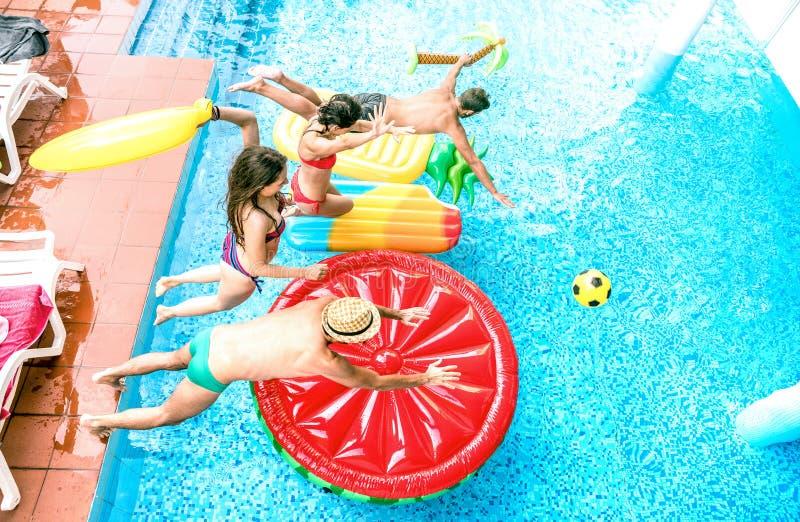 跳跃在游泳场党-青年与愉快的获得人和的女孩的假期概念的大角度观点的millenial朋友乐趣 免版税图库摄影