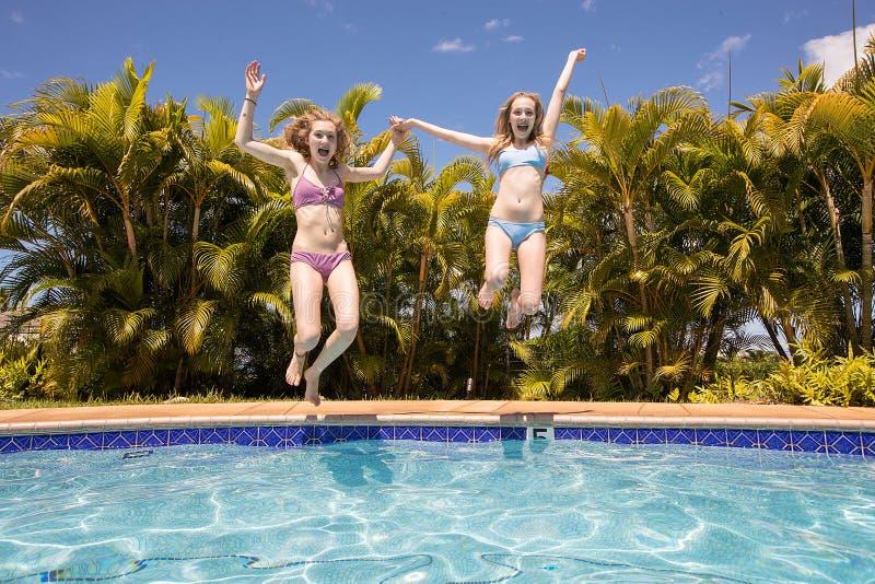 跳跃在游泳池的两个十几岁的女孩 图库摄影