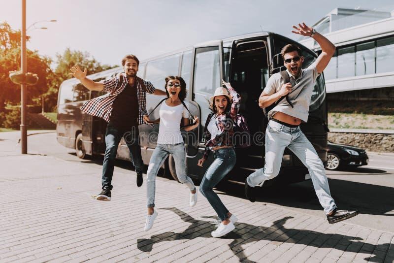 跳跃在游览车前面的激动的年轻人 库存图片