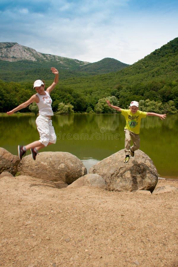 跳跃在湖附近的母亲和儿子 免版税图库摄影