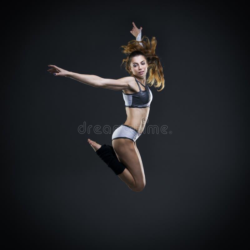 跳跃在演播室的美丽的少妇舞蹈家 免版税库存照片