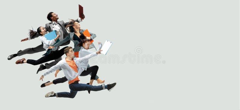 跳跃在演播室背景的办公室工作者 库存图片