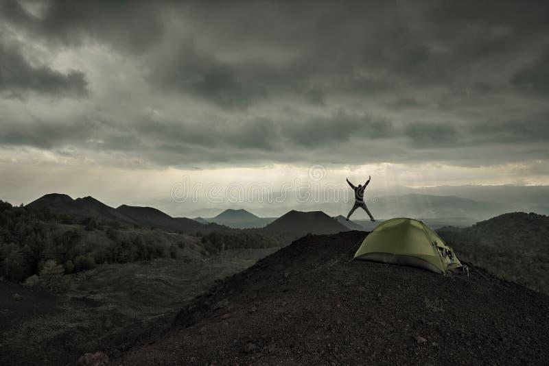 跳跃在火山的风景的剧烈的天空下的人剪影由狂放的阵营在Etna公园 免版税图库摄影