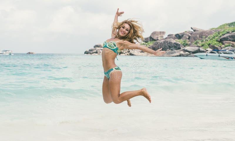 跳跃在白色沙子的美丽的妇女 免版税库存图片