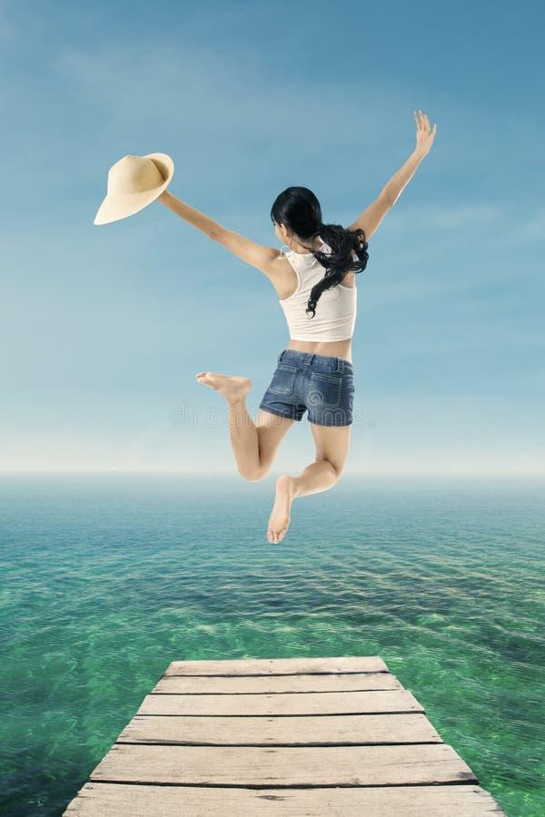 跳跃在码头的少妇 库存照片